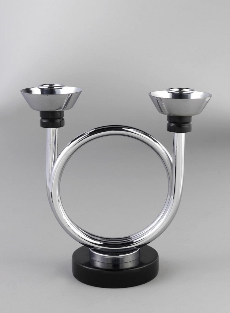 Candelabrum in form of a coiled musical horn with ends terminating at candle holders, resting on a black disk base.