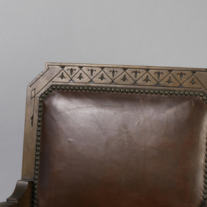 Upholstered seat and back with decorative brass nail heads, incised decoration on wood frame, the seat supported on diagonal front legs reinforced by a turned stretcher, slightly splayed back legs rise to seat back.