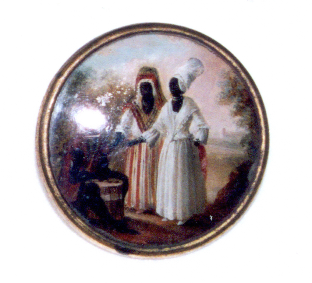Button depicting scene of three figures in a tree-filled landscape with possible field or clearing in background. A seated man on left playing a drum is pointed at by two standing women, one is striped and the other in white dress.