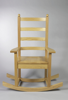 Rocking chair with rockers at the front to legs and back to legs, making the chair rock sideways. Ladder back topped with two spherical finials, and seat with indentations for sitting. Flat topped armrests.