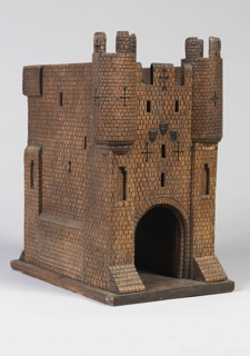 Castle model reminiscent of fortified brick with two crenellated watchtowers and large arched opening.
