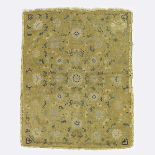Cushion cover of yellow silk tapestry with a radiating design of small chrysanthemums in off-white and blue with touches of red. With birds, scrolls, and other flowers. Lined with yellow silk damask. Yellow and white silk fringe on all sides.