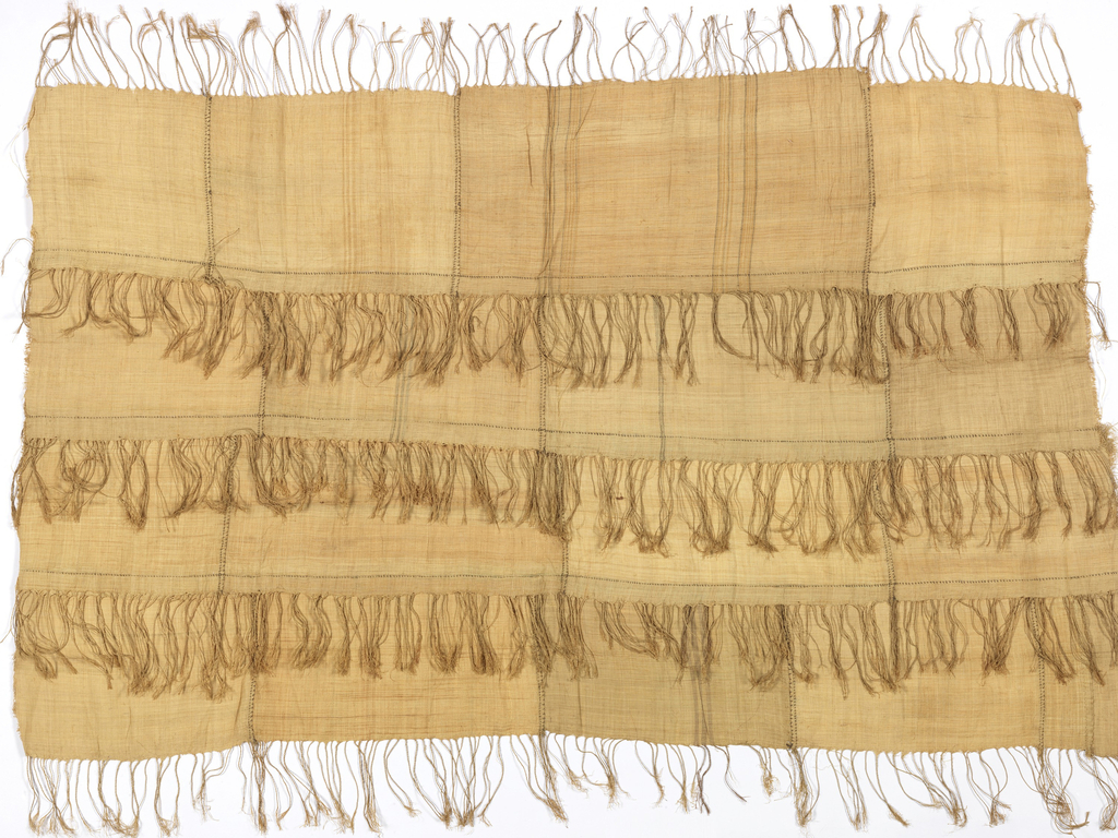 Rectangular panel composed of four strips of woven raffia with twisted warp fringes. Each strip is composed of smaller pieces, stitched together with dark raffia strands.