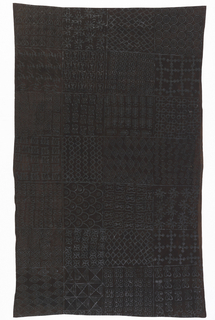 Woman's cotton wrapper, dyed dark brown and printed with hand-carved stamps in a dark glossy ink. The cloth is divided into a grid of four by seven squares; each square is printed with a single geometric pattern. The motifs are carved on fragments of calabash gourd, then stamped on fabric in a technique called adinkra.