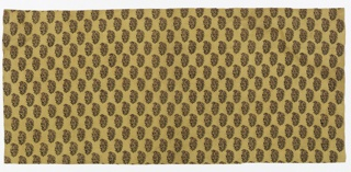 Fragment of block printed cotton in green, brown and red on light brown ground. Pattern allover showing stylized floral bouquet.