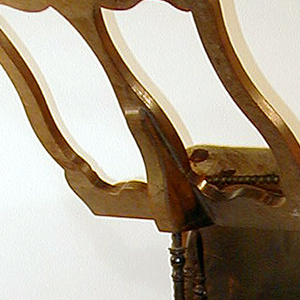 Four straight cylindrical turned legs on inverted turnip-shaped feet; one leg to front. Eight cylindrical stretchers below the straight seat rails. Back and seat fully upholstered in black leather nailed over hair and burlap. Cresting is an upholstered semicircle. Seat is rhomboid, one acute angle to front. Wrought iron moveable bracket attached to right upright of tub-like back supports scrolled wood reading rack. A provincial style.
