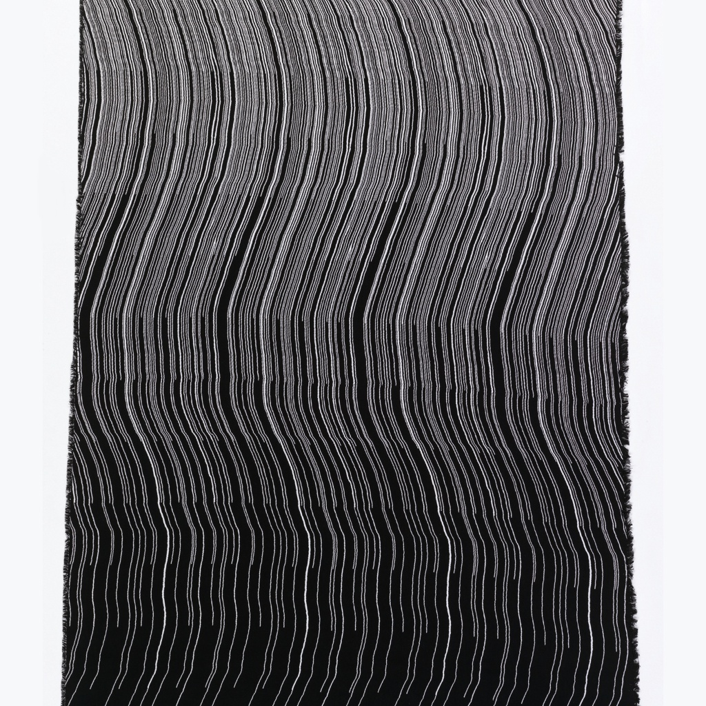Length of woven cotton with white and black undulating vertical lines. Gradual color transition from predominantly white at one end to predominantly black at the other.