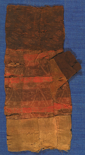 A complete but fragile woven silk mitt, with bands of dark reddish-brown, orange-brown, and ochre, with damask-type patterning.