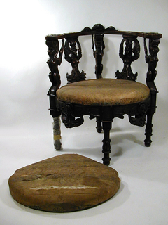 Chair has four turned and carved legs, arranged with one to front.  Legs support a seat rail enriched with masks, scrolls, and floral swags from which three grotesques and two winged female half-figures that support the semi-circular arm of the chair.  Chair's back cresting is carved with floral scrolls and a knot of flowers.