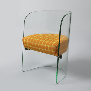 Tub-type armchair formed from single upright curved sheet of thick transparent plate glass with D-shaped seat cushion upholstered in woven fabric with orange and yellow grid pattern (not original); seat supported by three metal fittings inserted through glass on left and right sides, and back.