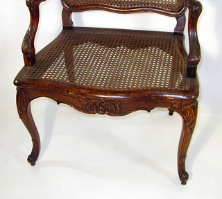 Curvate rectangular back, caned, posts and rails chanelled; crested with a rocaille ornament.  Curved arms, stumps carved with coarse leaf forms.  Caned seat rails are serpentine, carved with shell and scroll designs.  Cabriole front and rear legs, scrolled feet.