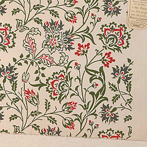 Stylized flowers and leaves on curving stems, printed in blue, green, and red on a white ground.