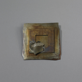 Flat brooch is square, with base of hammered, patinated sheet copper with irregular edges. Applied over base is square of silver engraved with grid pattern. Center of silver pierced with square; soldered to square is irregular metal form with stylized fret pattern. Pin clasp soldered to reverse.