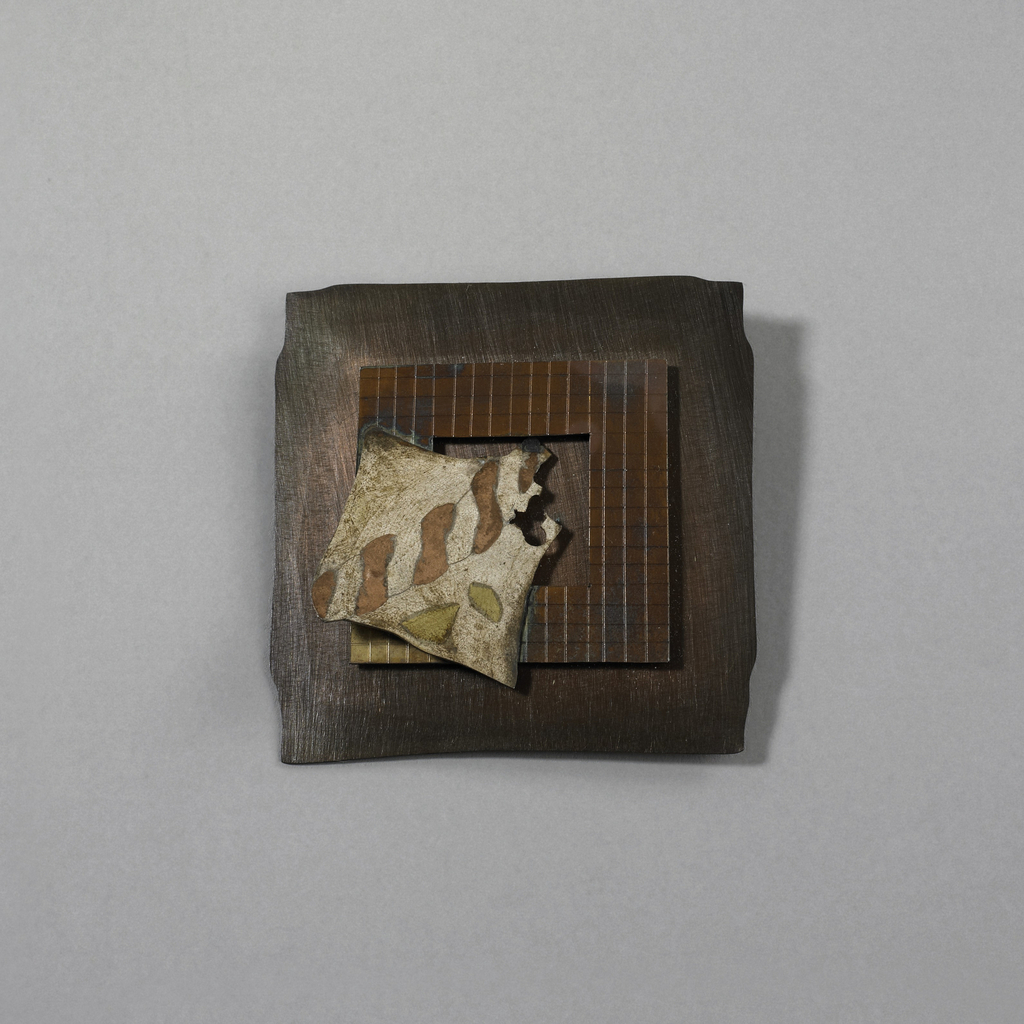 Flat brooch is square, with base of hammered, patinated sheet copper with irregular edges. Applied over base is square of metal engraved with grid pattern. Center of square pierced with square opening; applied over piercing is irregular form in silver with abstract inlays of copper and gold. Pin clasp soldered to reverse.