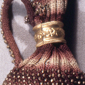 Small purse in the form of a jug, in ombre stripes from brownish-red to white. With bronze-colored beads, a gilt ring at neck, and gilt drop at botton.