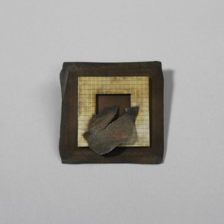 Flat brooch is square, with base of hammered, patinated sheet copper with irregular edges. Applied over base is square of silver engraved with grid pattern. Center of silver sheet pierced with square; applied over square is irregular sheet of deeply patinated metal. Pin clasp soldered to reverse.