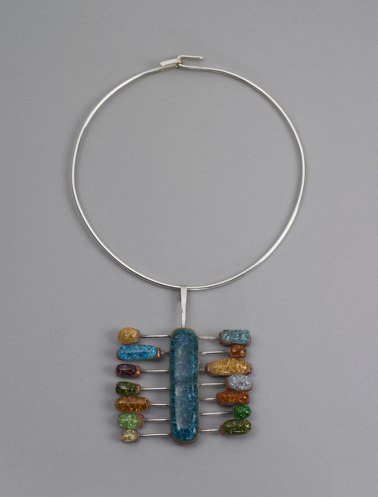 Pendant is composed of glass and ceramic oval beads on silver prongs radiating from central elongated oval bead, which hange from a silver circle.