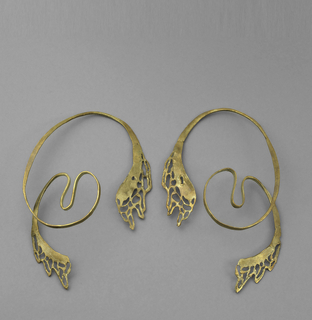 Gold earrings formed into abstract curved elements. From bottom, lace-like dripping effect leading to a loop and two arches, then looping over entire earring and terminating at another lace-like dripping element.
