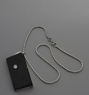 Rectangular ebony cover of silver locket (a) bottom, has moonstone on face, and hangs from silver chain (b) of small cylinders.