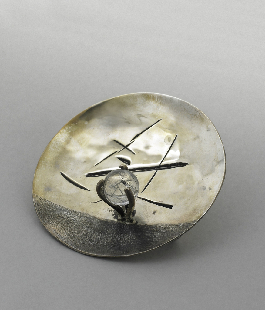Silver brooch in shape of curved disk with some scratch-like decoration on face and prongs holding a quartz sphere.