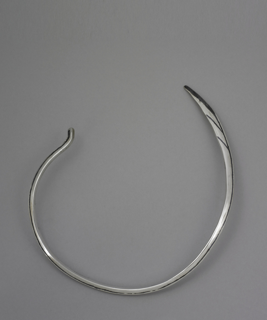 Curved piece of silver with black line along front. One end is rounded and the other flat. Necklace is open at back; no closure.