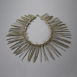 Necklace with radiating pendants made of wooden sticks, some terminating in pearls; interior, metal spirals ending pearls.