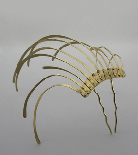 Hair ornament with two wavy pins. Long curved gold strips of various lengths, that seem to be bolted to main horizontal support, project at different angles, but all in the same arc form.