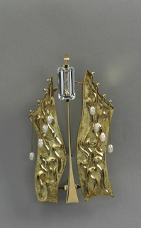 Two strips of gold, molded with decoration, each draped with pearls hanging from gold pins at the top. These strips flank a thin piece of gold at the center which is topped with an emerald-cut aquamarine.
