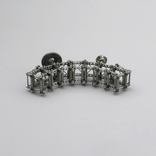 Brooch composed of arced ladder-like construction with rivets, bolts and wires.