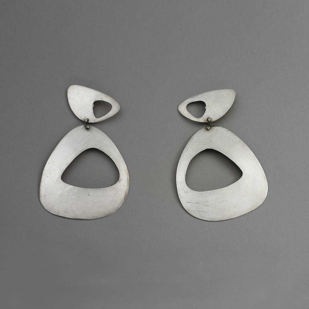 Earrings shaped like rounded triangles with void at center in the same shape; similar shape as larger pendant.