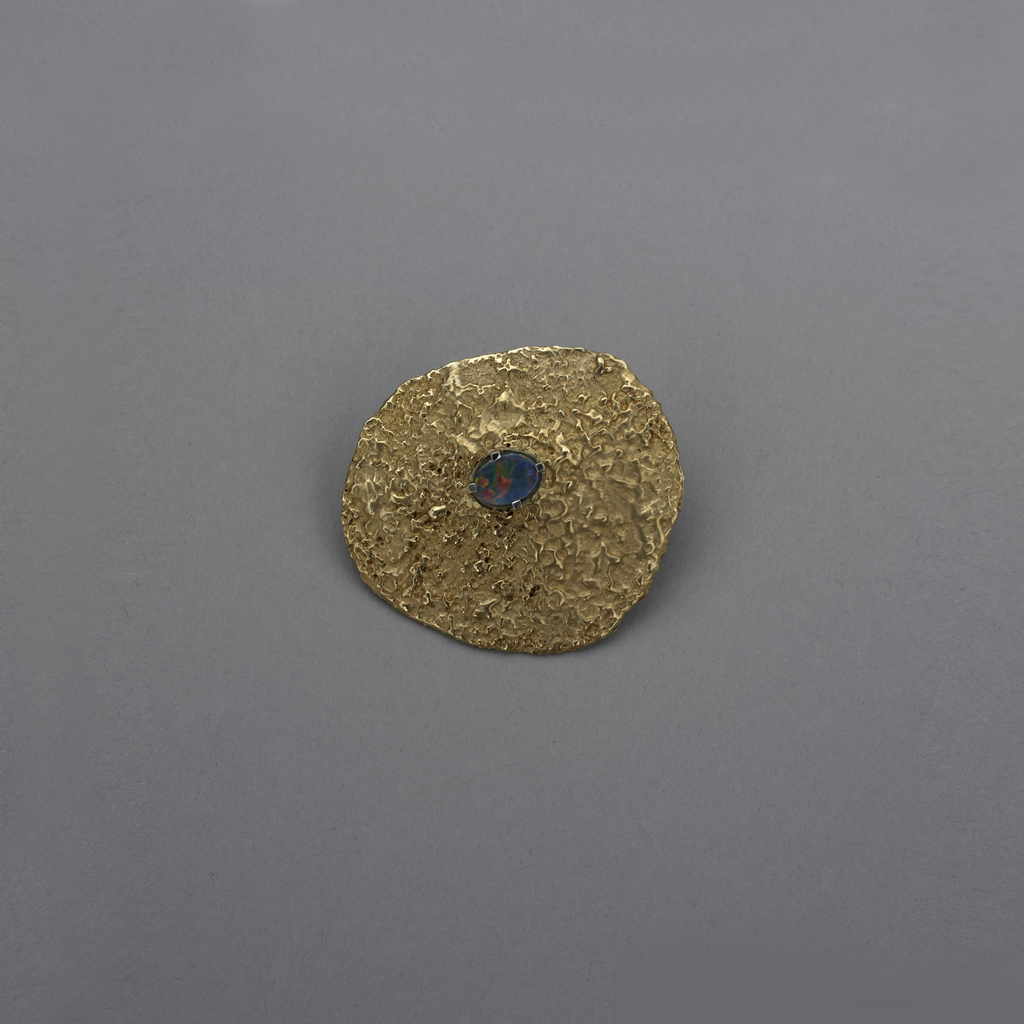 Roughly circular flat gold brooch with corrugated and rough surface; at center, oval blue opal with square prongs.