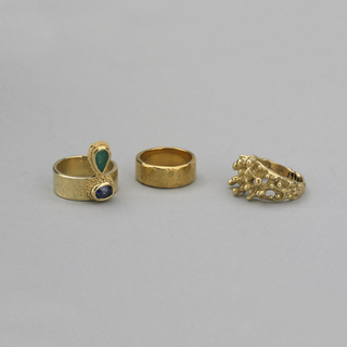 Hammered gold band with oval-shaped sapphire and crowned with teardrop emerald, both framed with gold granulation.