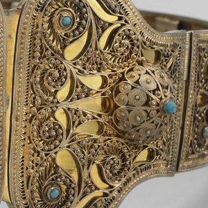 Belt with open filigree work with turquoise stones and semi-spherical caps throughout, on flat backing.