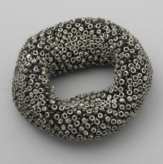 Thick flexible circle composed of hundreds of tiny coiled elements attached to chain mail-like armature.