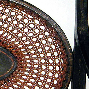 Curved and sloping armrests; top and lower seat rails include an oval caned medallion with a central oval panel painted en grisaille with a woman and child.  Curved arms are received by stumps extended vertically to straight, tapered, turned front legs.  Seat caned, burgundy colored caning.  Gilded and toned decoration of conventionalized flowers and leaves, and bandings, on black ground.