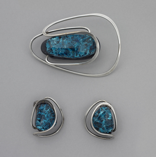 Two silver earrings, each with central glass piece. Oval piece in deep turquoise cradled by silver strip looping over and around.