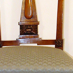 Rectangular open back; top rail composed of two swags centering a bowknot.  Posts are carved with pendant garlands.  The splat is an obelisk-form surmounting a square rosette.  Front role of upholstered seat is carved with ribbons and pendant swags.  Front legs are square, tapered and fluted; rosettes at knees.