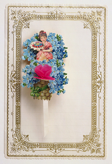 Inside an ornamented gilt frame is a sheet of lined note paper, with a basket of forget-me-nots, a paper heart and a girl, attached, upper left. On a double sheet of paper, folded in half, horizontally.