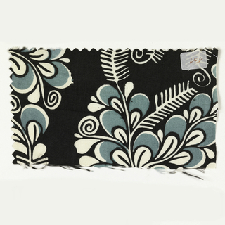 Abstract floral pattern in green and white on a black ground.
