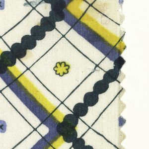 Diagonal plaid with very small flowers, hearts and crosses in center squares; (a) black, purple, blue, and yellow-orange on ivory; (b) dark green, blue, and yellow on ivory.