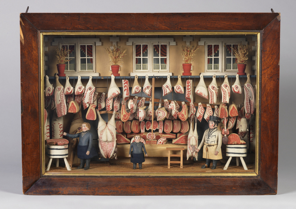 Model of a butcher shop composed of a shadow-box, glass-faced, enclosing longitudinal shelf and rack, above center of box hung with carved and painted joints of meat. At center back: a stand with other cuts of meat; to left and right, butchers' blocks. At front: three figures: two men and a boy. Across top, likeness of a facade with three double windows.