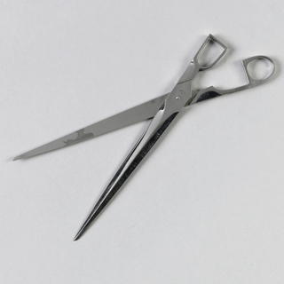 Scissors with sharply pointed blades and handles in angular shapes.