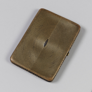 Rectangular clutch covered in gilt pattern of concentric almond shapes, metal clasp.