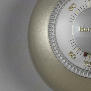 Dome-shaped, matte gold plastic housing surrounding circular thermometer with clear plastic dial.  Raised gold callibration numbers on upper and lower portions of thermometer.