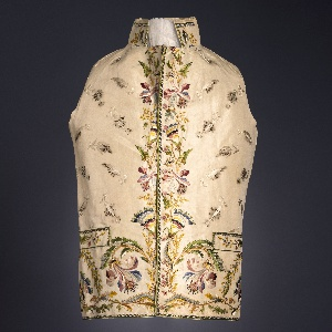 Gentleman's waistcoat with standing collar, straight hem edge and pocket welts, with ten worked buttonholes and covered buttons, lined with twill. Embroidered in twenty-five colors of silk floss and chenille on an ivory silk taffeta ground. Overall small floral sprig, with a deep border of irises and other flowers down center front and across bottom. On the larger flowers at the bottom, caterpillars are embroidered in various shades of chenille.