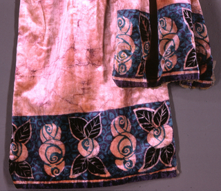 "Long stole with triangular middle-section ending in elaborate tassel of metal, jet and silk. Pink velvet with ""batiked"" effect in purple. At either end, printed border of sylized flower forms in black, green and purple. Lined with grey chiffon."