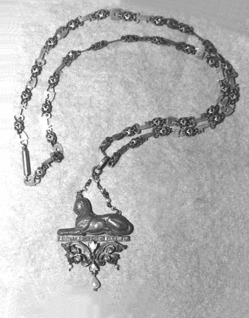Chain of cross-hatched oval beads with locks and keys as links; jasper pendant in form of a sphynx in profile, set in enameled silver and attached to silver chain beaded with six small pearls; sphynx sits on bar set with twelve blue facetted stones surmounting a floriated scroll enamelled in light and dark blue, green and red.  Red stone in center from which hangs a large pearl flanked on either side by two smaller pearls.