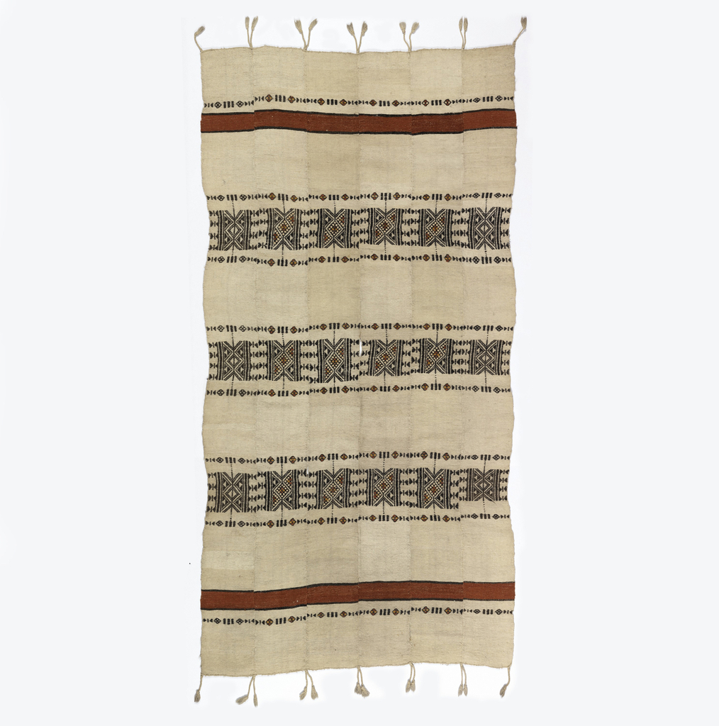 Panel composed of six strips stitched together, fringed on two warp ends. Red stripes at top and bottom with three bands between patterned with triangle and diamond forms, in black, yellow and red on an undyed wool ground.