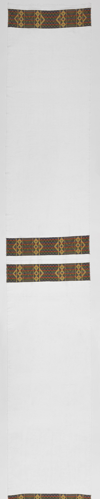 Long panel of sheer white cotton with a 6 3/4 inch border at both ends and two woven bands across the middle of the panel. Bands and borders are a geometric pattern of triangles, diamonds and chevrons in  blue, green, gold and red.
