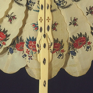 Cockade fan with a pierced bone handle and slender sticks supporting twenty-four silk ovals, each with sixteen scallops, all edges rolled and whipped. Each leaf is decorated at three points with brocaded colored silk flowers, and attached to the guards by a slender stick on back. The two end ovals adhere to guards that have portions sliding in groove, forming handle. Inner ends of sticks pivot on a metal rivet with mother-of-[earl washer.